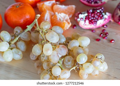 Autumn winter fruits: grapes, tangerine and pomegranate.