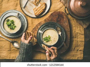 Autumn, Winter home dinner. Flat-lay of Fall warming celery cream soup and female hands with grilled bread over linen tablecloth, top view. Comfort food, vegetarian, healthy and slow food concept