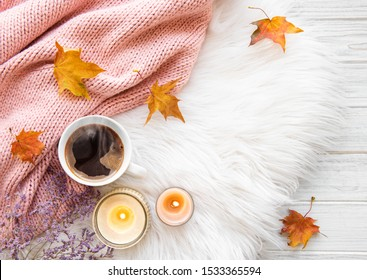 Autumn and winter home still life . The view from the top. The concept of home atmosphere and decor. Cup of coffee and autumn leaves on fur background