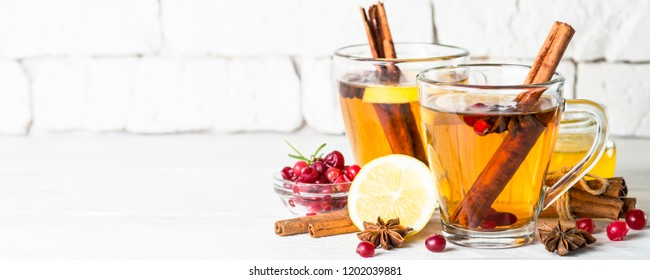 Autumn or winter hot tea with fruit, berries and spices in glass cup.