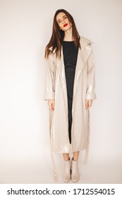 Autumn, winter or spring trendy outfit woman in stylish beige lacquer trench coat and black dress. Beauty fashion portrait of brunette woman with natural make-up and red lips put on coat.
