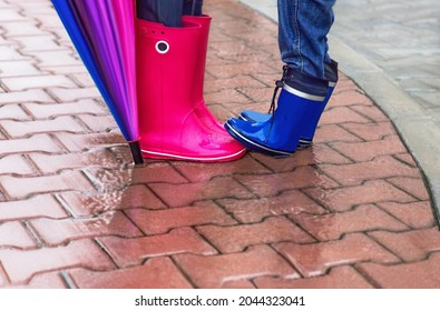 Autumn. Woman and child wearing rubber boots and have umbrella. They having fun in rainy day. Street, city. Protection in the rain. Concept about activity, leisure, travel. Copy space. Selected focus.