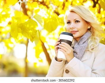 Autumn Woman with Coffee Cup. Fall. Blonde Beautiful Girl and Yellow Leaves in the Park