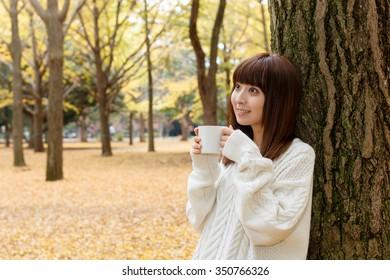 Autumn woman drinking coffee under fall foliage