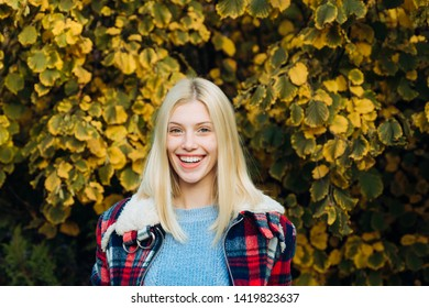 Autumn woman. Hugge soft concept in clothes. Smiling young woman in park. Trees with yellow leaves. Cozy autumn