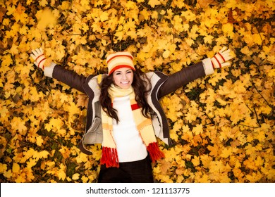 autumn woman lying over leaves and smiling, top view