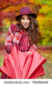 Autumn woman in autumn park with red umbrella, scarf and leather gloves