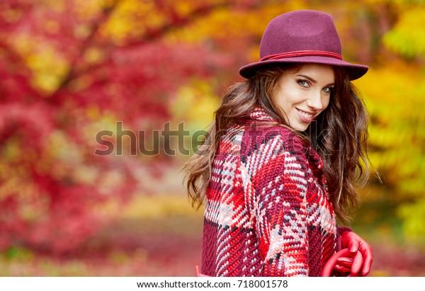 Donna autunnale nel parco autunnale con ombrello rosso, sciarpa e guanti in pelle