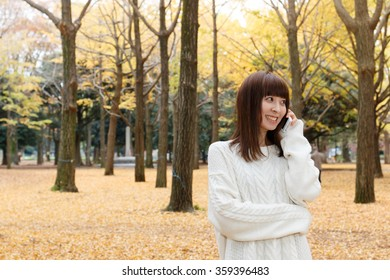 Autumn woman talking on mobile phone in fall