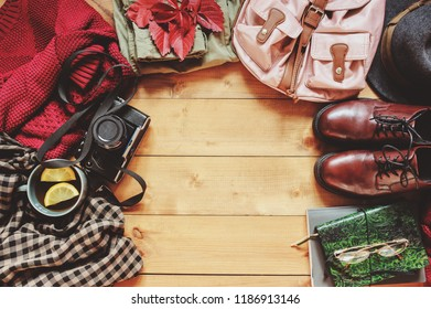 autumn women fashion clothes set with cozy sweater, shoes, plaid shirt, vintage photo camera, backpack and cup of tea. Fall seasonal walk concept, flat lay with empty space