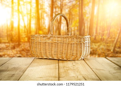 autumn wooden table with a wicker basket for an advertising product