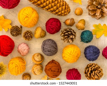 Autumn wool composition with balls of yarn, acorns, pine cones and fall leaves. On a rustic background. Top view.