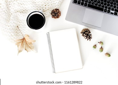 Autumn workspace composition. Notebook mock-up scene. Cup of coffee, wool blanket and laptop on white table background. Fall design. Flat lay, top view.