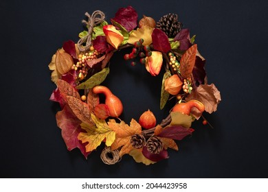 autumn wreath of fruits and leaves on black, cozy autumn design, thanksgiving background, autumn welcome concept