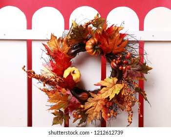Autumn wreath hanging on a white fence
