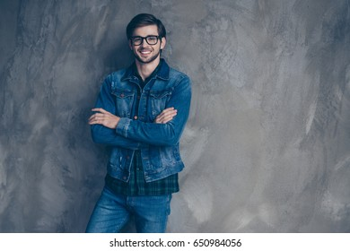 Autumn. Young excited student  in casual jeans outfit is standing on a concrete wall`s background, wearing glasses and smiling with crossed hands