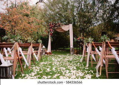 Autumnal arch for the wedding ceremony decorated with roses, apples, grape and pomergranate