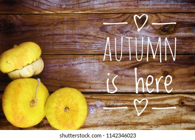 Autumnal background with pumpkins on old wooden table with the text 'autumn is here'