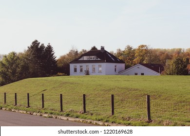 Autumnal countryside landscape in Lower Saxony, Germany showing two white houses with tiled roofs standing behind a dike in idyllic environment, road in the foreground, copy space for text