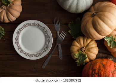 Autumnal Halloween or Thanksgiving table setting. Fallen leaves, pumpkins, an empty plate and vintage cutlery on a wooden table. Thanksgiving background. Top view, toned image