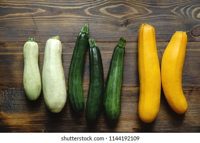 Autumnal harvest squash and zucchini variety on wooden background. Top view