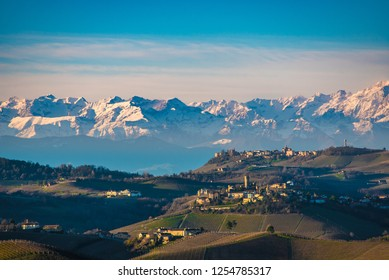 Autumnal hills and vineyards in Langhe Monferrato region with mountains on background in Piedmont, Northern Italy.