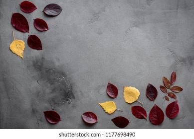Autumnal minimal composition. Pattern made of red and yellow fall leaves on dark background, autumn concept. Flat lay, top view.