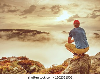 Autumnal misty morning in wild nature. Hiker in sports wearing stand on sharp peak and watching natural show in valley bellow.