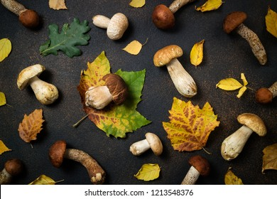 Autumnal mushrooms background. Mushrooms boletus, orange-cap boletus mushrooms and autumn leaves on brown table.  Autumn composition. Flat lay, top view