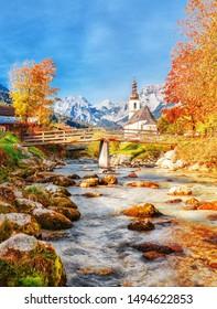Autumnal scenery of Ramsau National Park in Berchtesgadener Land in Bavaria, Germany. Incredible Alpine seasonal view of Parish Church of St. Sebastian. River Ramsauer Ache flowing Germany, Austria.