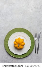 Autumnal serving plate at gray background with fork and knife with yellow decoration as pumpkin
