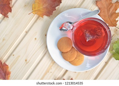 Autumnal setting with tea on a wood background - A teabag of fruit tea floats in a glass cup, next to it are cookies and dried autumn leaves