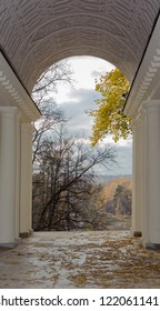 Autumnal trees and pond view through colonnade in museum-reserve Tsaritsyno. Russia, Moscow, October 2018