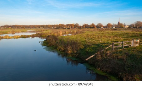 Autumnal view at the small Dutch river Mark and the outskirts of the village of Ulvenhout
