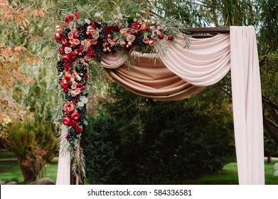 Autumnal wedding arch decoration of roses, apples, grape and pomergranate