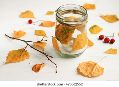 Autumn-themed DIY candle. Tealight candle in glass jar, decorated dried golden leaves. Fall time interior decor.