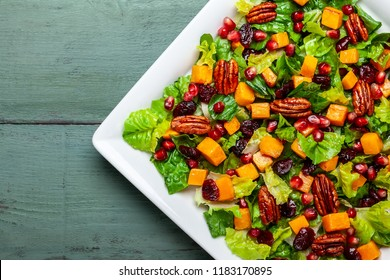 Autumn-winter season salad with roasted pumpkin, dried cranberry, pecan and pomegranate seeds.A Great choice for Thanksgiving, Christmas or any other winter holiday menu. Healthy eating concept.