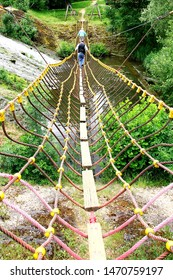 Auvergne France May 2017. Long view of rope bridge with narrow planking used as walk way. Thick red rope secured by yellow plastic tethers. Two men walking away over bridge. Foliage and river beneath