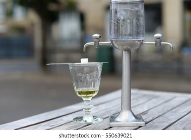 AUVERS-SUR-OISE, FRANCE - JULY 14, 2016: Traditional way to serve absinthe, also called the green fairy, a French anise flavoured spirit. Water drips in the highly alcoholic drink before consumption
