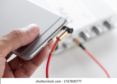 AUX cable connected between smartphone and mini amplifier. Cable for stereo input and output.