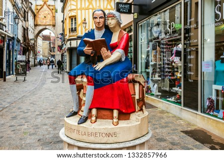 AUXERRE, FRANCE - 1st March 2019. Shopping street, clock tower and a painted statue representing a man and a woman reading, sitting on a pile of books.