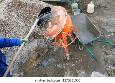 auxiliary worker uses a shovel to prepare a cement mortar on a construction site