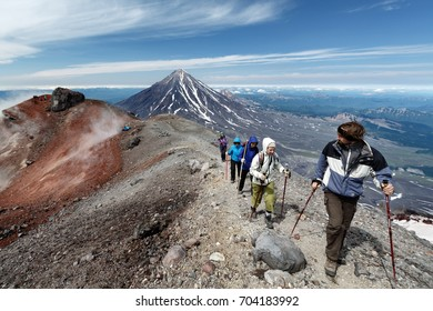 AVACHA VOLCANO, KAMCHATKA PENINSULA, RUSSIAN FAR EAST - AUG 7, 2014: Group of hikers climbing along the edge of summit crater of active Avachinsky Volcano on background of cone of Koryak Volcano.