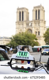 Available taxi (green light) in Paris with Notre-Dame cathedral on the background.