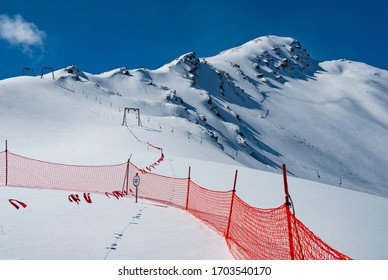 Avalanche warning sign and net fence in Caucasus mountains on the Mount Cheget background. The inscription on the warning sign in Russian means Slope Closed.