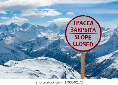 Avalanche warning sign and net fence in Caucasus mountains on Mount Elbrus background. The inscription on the warning sign in Russian means Avalanche Hazard.