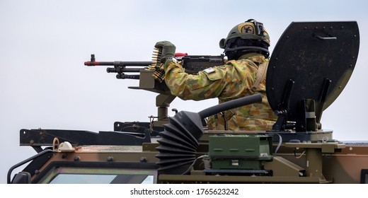 Avalon, Australia - February 27, 2015: Australian Army soldier with large machine gun in the turret of a Bushmaster armoured Personnel carrier (APC).