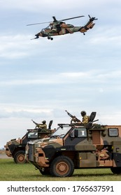 Avalon, Australia - February 27, 2015: Two Australian Army Bushmaster armoured Personnel carriers (APC) with an Army Eurocopter Tiger helicopter providing air cover.