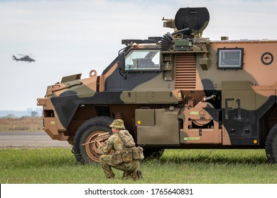 Avalon, Australia - February 27, 2015: Australian Army soldier with a Bushmaster armored personnel carrier (APC) and an Army Eurocopter Tiger helicopter.