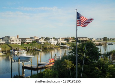 Avalon, New Jersey – July 18, 2014: An American flag in front of a row of luxury waterfront vacation homes on the back bay in Avalon, New Jersey.